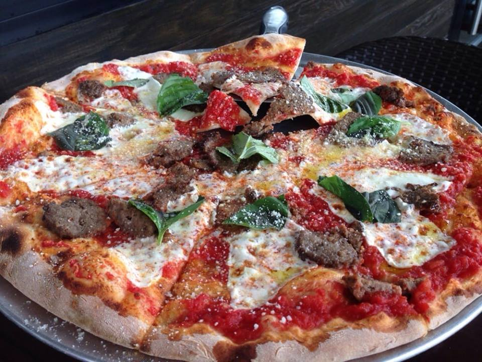 Cheese pizza pie topped with meatballs and basil.