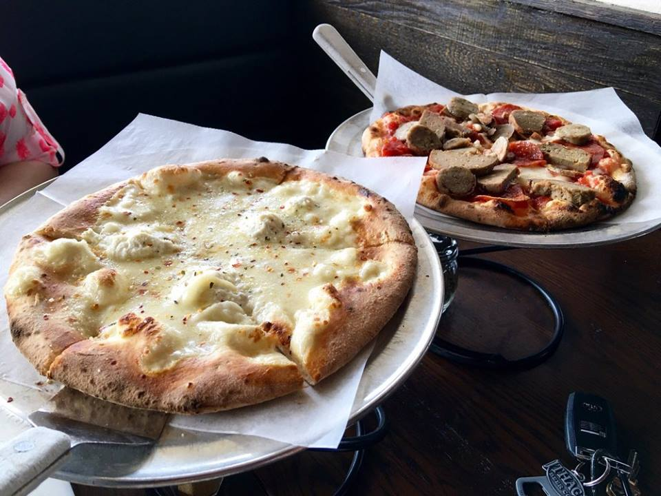Two pizzas: One a traditional white pizza and the other a pie with meatballs and cheese.