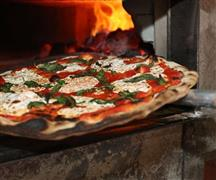 Original Coal Oven Pizza coming out of the oven fresh.