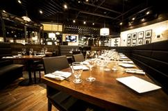Patsy's Dining room. Wood tables, black booths and white subway tiles.