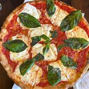 Original Coal Oven Pizza with oregano leaves on top.