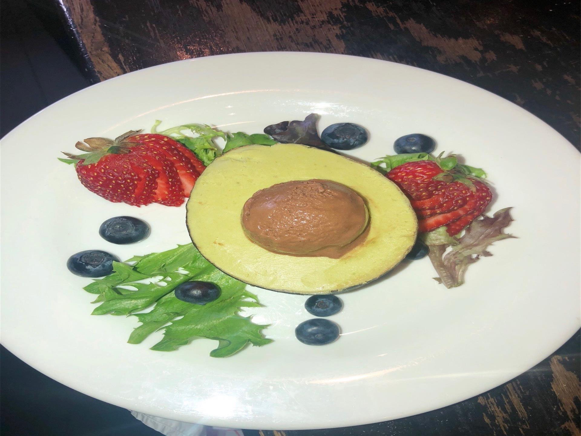 chocolate iccream in an avocado with strawberries and blueberries