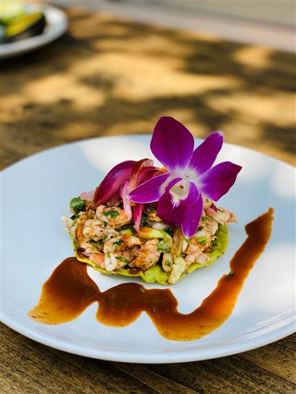 shrimp ceviche with edible flower garnish and guacamole