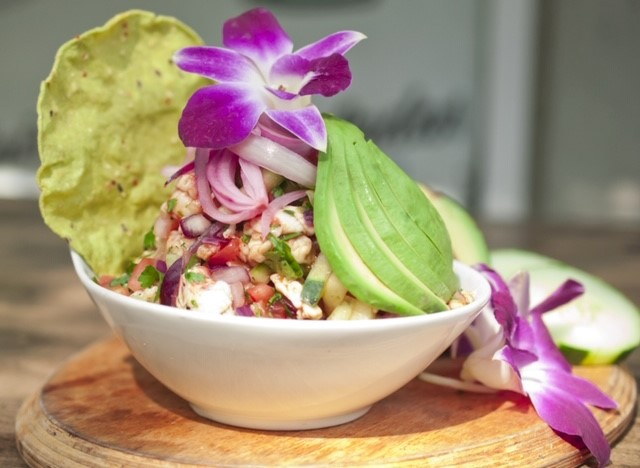 mix of beans, tomato, cilantro, onion, and other veggies in a bowl with sliced avocado and edible flower garnish