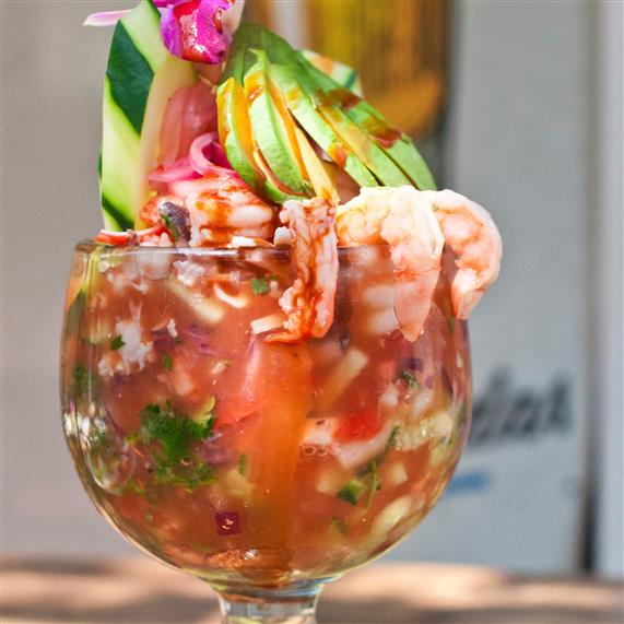 ceviche in a glass cup with shrimp, cucumbers, avocado