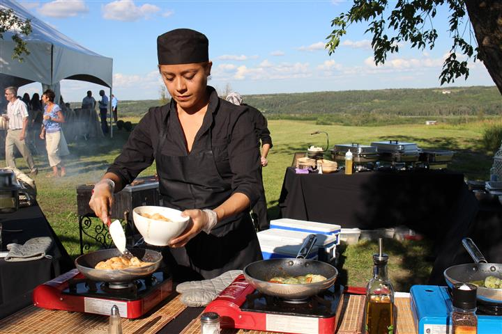 Member of staff preparing food at a hot kitchen station outdoors