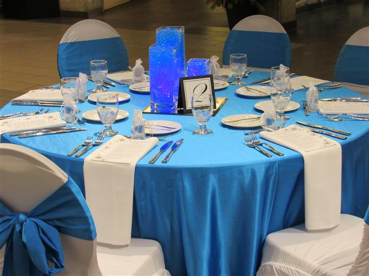 Round table set in light blue linen and decorated in blue details for an event