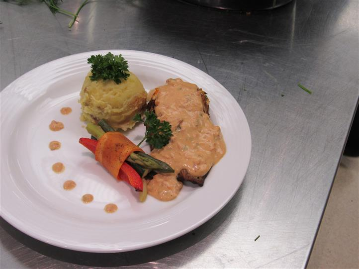 Dish served with a ball of mashed potatoed and grilled vegetables decorated with dressing