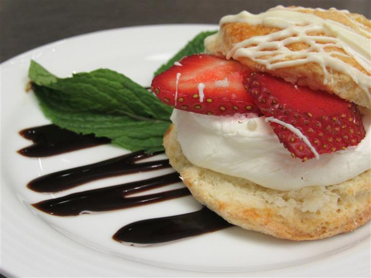 Open faced muffin filled with cream and strawberries served with chocolate syrup and mint leaves