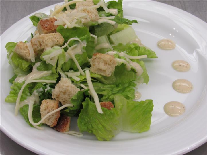Caesar salad topped with shredded cheese and decorated with Caesar dressing