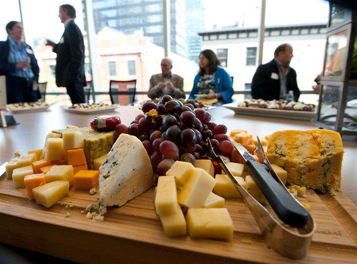 Cheese board with red grapes in the middles and people sitting at a table in the background