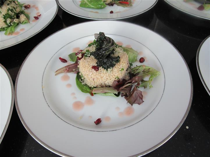 Quinoa salad shaped into a patty served with mixed greens drizzled with dressing