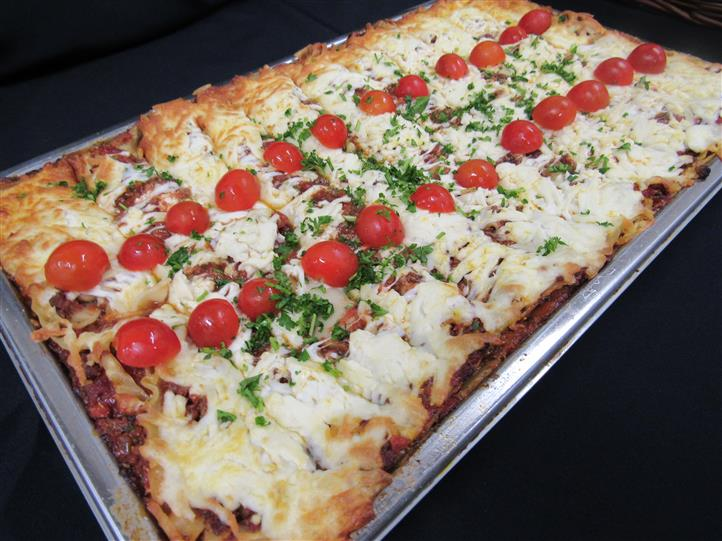 Oven baked dish topped with melted cheese served in the pan and garnished with cherry tomatoes and parsley