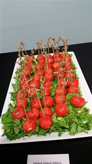 Tray of roasted cherry tomatoes filled with cheese on a bed of lettuce