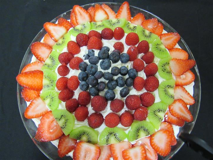 Fruit platter with a medley of fresh fruit arranged in circles on top of cream
