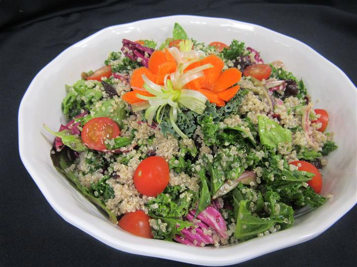 Tabbouleh salad with mix of red greens and other begetables topped with bulgur