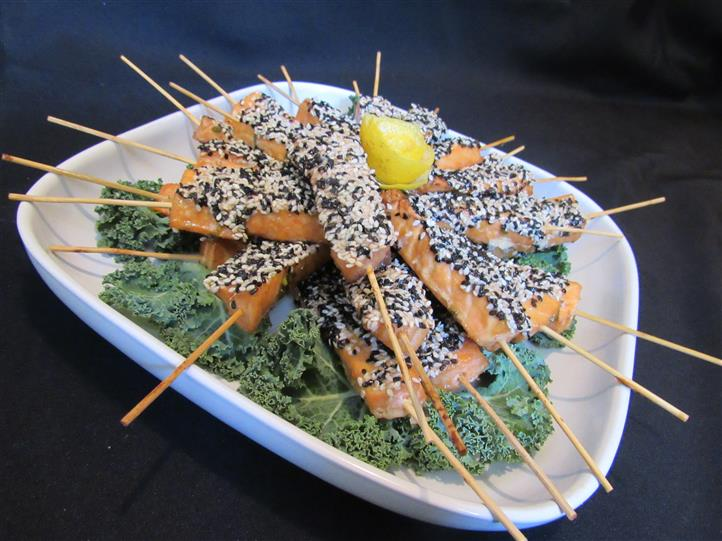 Fish skewers coated with black and white sesame on a bed of kale