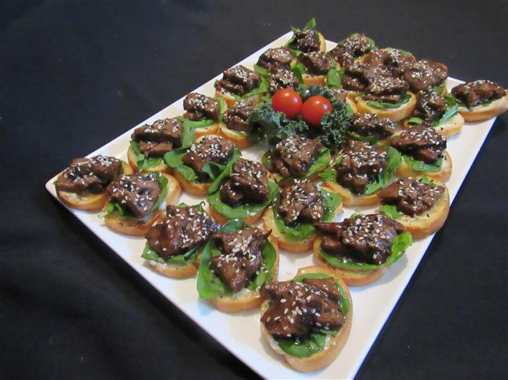 Platter with mini bruschetta canapes topped with meat