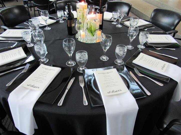 Black and white table setting for formal event with candles as the centerpiece