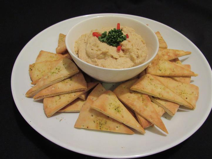 Hummus dip served with pita triangles for dipping