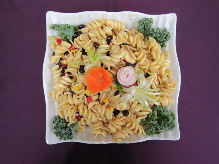 Colorful pasta salad decorated with kale and carrot
