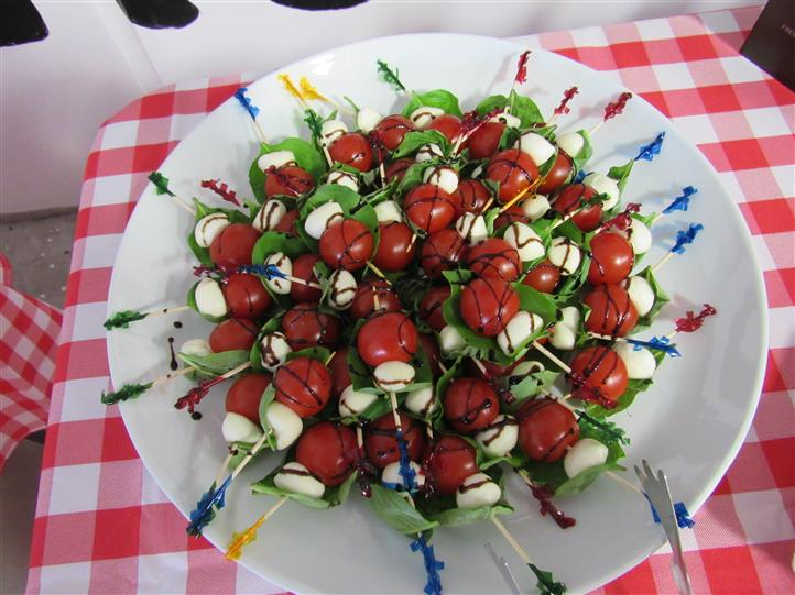 Mini Caprese salad skewers with cherry tomatoes, mozzarella cheese bites drizzled with balsamic