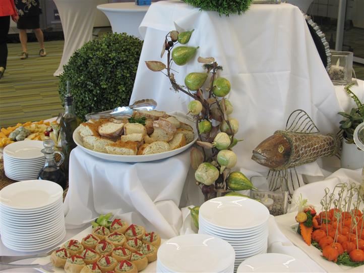 Detail of a buffet table set in white linen with a variety of platters with snacks and finger food