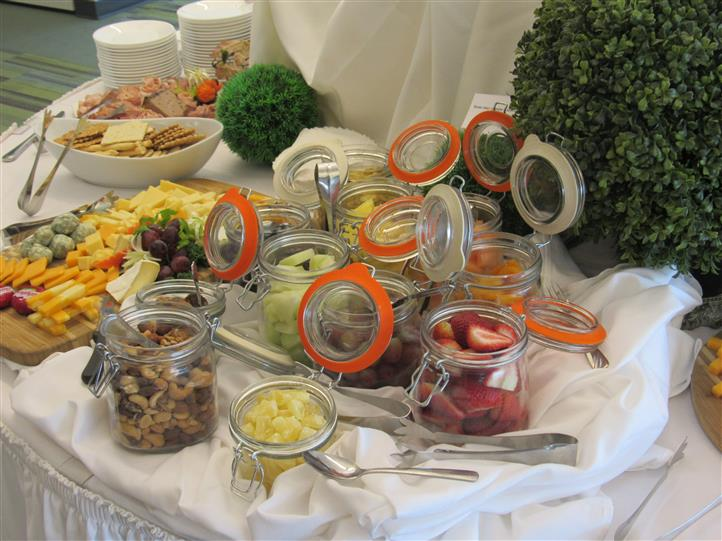 Glass jars with fruits and vegetables laid out in a catering station on a buffet table
