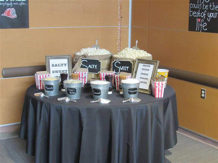 Pop corn station on a table with two big buckets of sweet and salty popcorn and various toppings to choose from