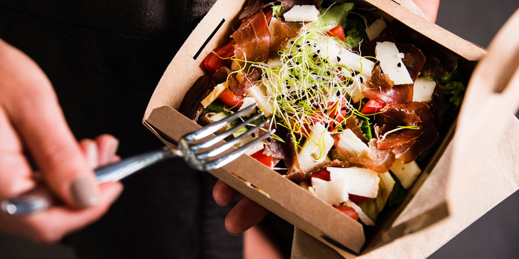 person holding a to-go container filled with food and a fork