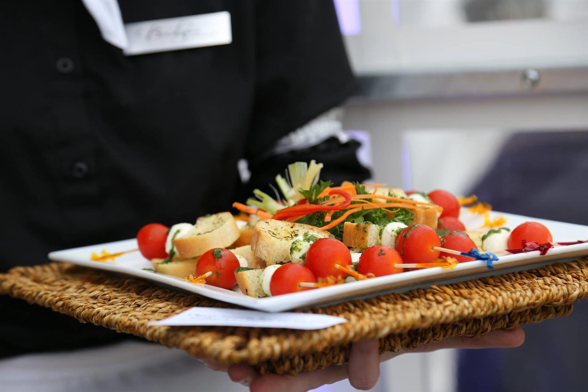 Server holding a tray of skewers with toasted bread