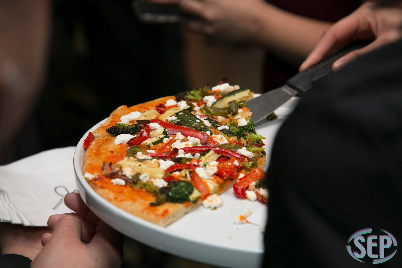 a person serving pizza on a tray