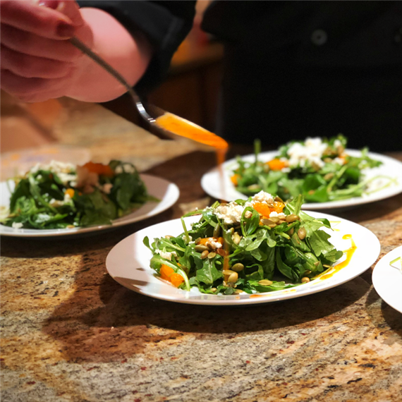 chef drizzling salad dressing on a plate of salad