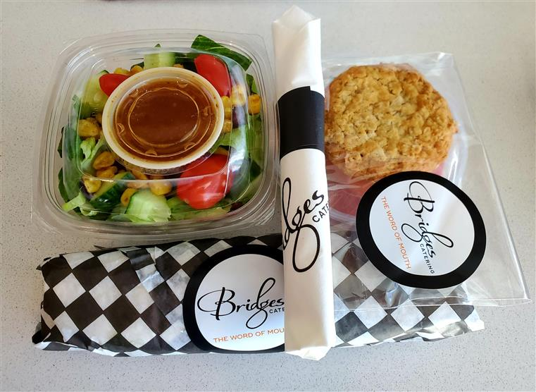 a salad, sandwich, dressing, and utencils in a to-go container