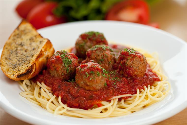 Spaghetti topped with meatballs, side of garlic bread.