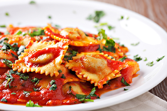 Raviolis with tomato sauce and parsley in dish.