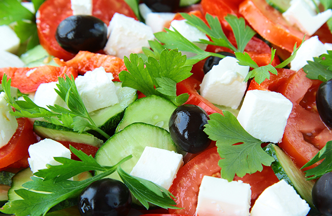 Fresh garden salad with cucumbers, black olives, cheese, tomatoes.