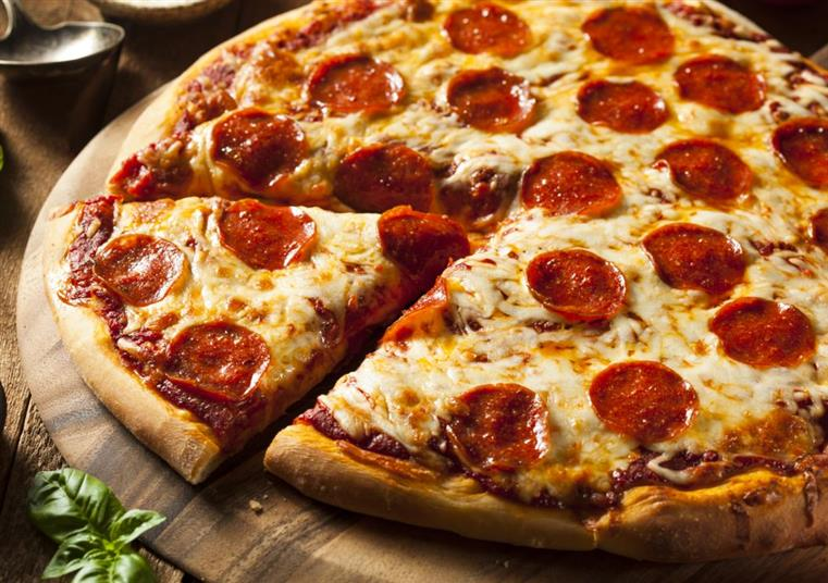 Pepperoni pizza with one slice cut on wood board.