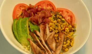 bowl with stripes of grilled chicken, avocado, cooked corn, bacon and tomato
