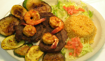 grilled beef and shrimp on a plate with grilled zucchini, lettuce, diced tomatoes and rice