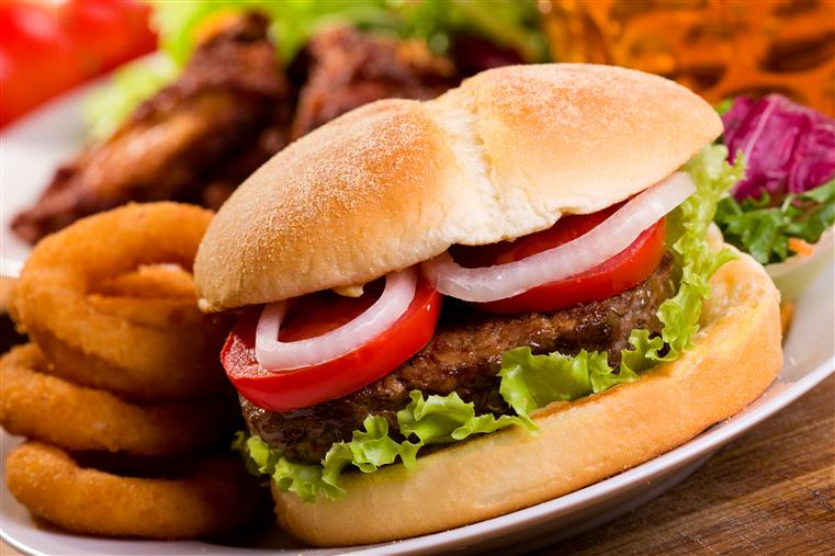 burger with lettuce, tomato and onion on a plate with onion rings