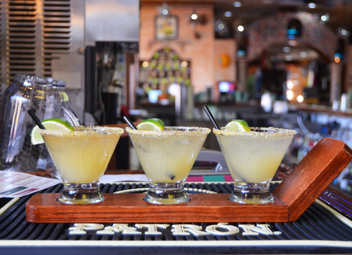 three drinks with straws and lime wedges on top of the bar
