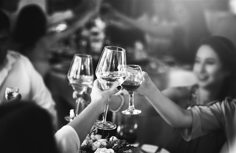 crowd of people toasting with wine glasses together