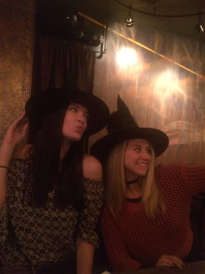 two girls posing while wearing witch hats