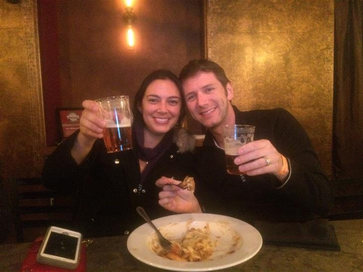 two friends holding up their beers and smiling with a plate of food