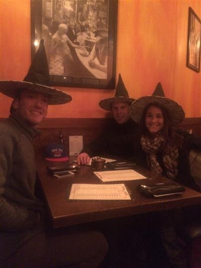 three customers smiling at a booth while wearing witch hats
