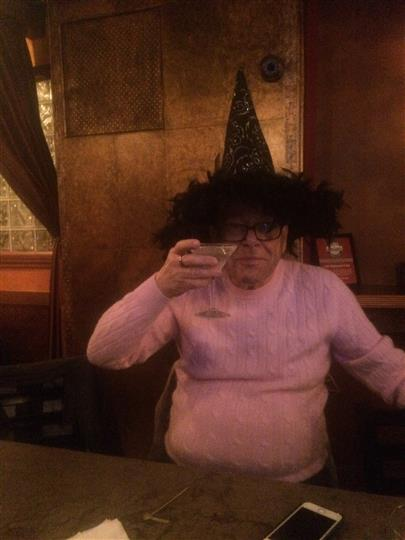 a customer holding up his martini while wearing a witch hat