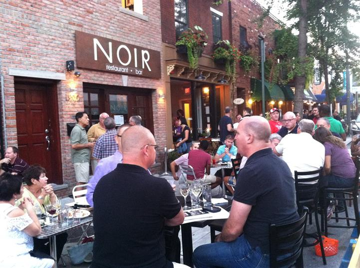 crowded outdoor seating area in front of noir