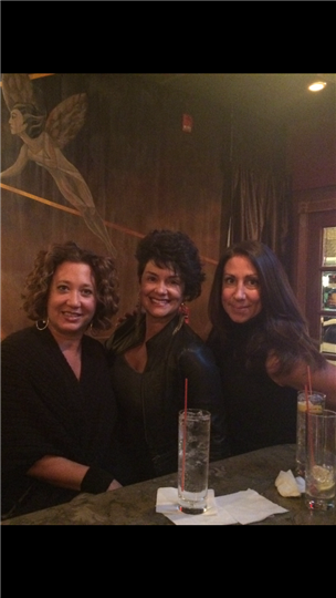 three women smiling and posing by the bar