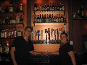 two bartenders smiling in front of a wall of liquor bottles